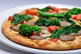 Pizza with rapini, tomato, and salami