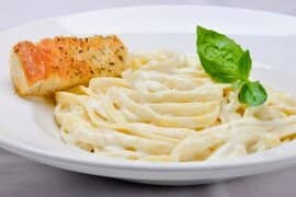 Fettuccine Alfredo with a slice of garlic bread