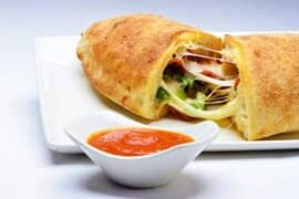 Panzarotti filled with cheese, pepperoni, and rapini with Marinara Sauce